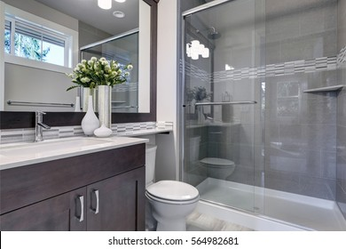 Bright new bathroom interior with glass walk in shower with grey tile surround, brown vanity cabinet topped with white counter and paired with mosaic tile backsplash. Northwest, USA