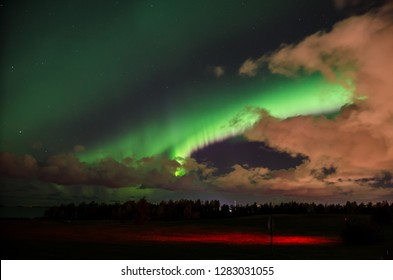 Bright northern lights in autumn behind orange clouds above Oulu city