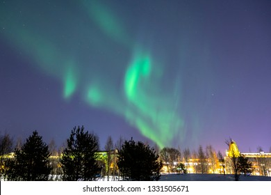 Bright northern lights on the clear starry sky in winter. Natural light show above the city of Oulu, Finland - phenomenon caused by particles flying from the sun during magnetic storm. February 2019