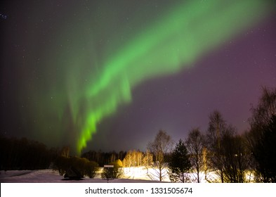 Bright northern lights on the clear starry sky in winter. Natural light show above park in Oulu, Finland - phenomenon caused by particles flying from the sun during magnetic storm. February 2019