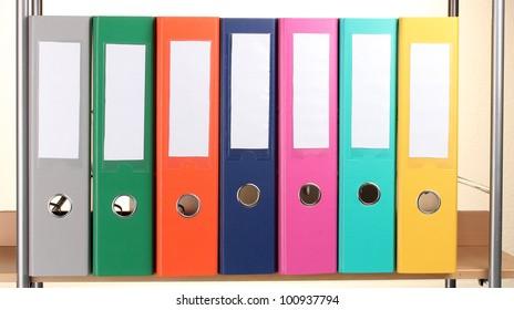 bright office folders on wooden shelf