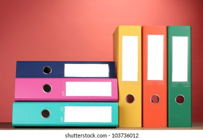 bright office folders on wooden table on red background
