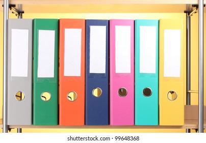 bright office folders on wooden shelf on yellow background