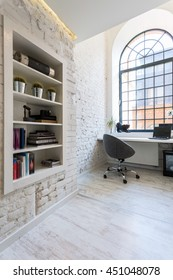 Bright office room with exposed brick wall, light flooring, simple desk and comfortable chair