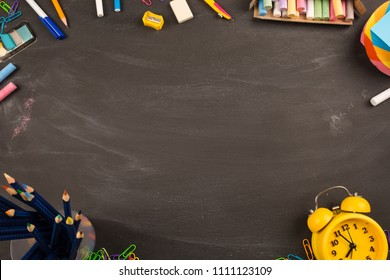 bright office supplies, yellow alarm clock on black chalkboard top view, copy space. concept: back to school, school's out, school holidays, teacher's day