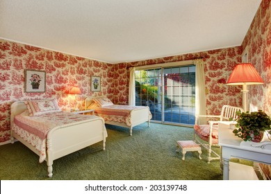 Bright old fashion bedroom with walkout deck, red wallpapers and green soft carpet floor. Furnished with antique beds, chair and table