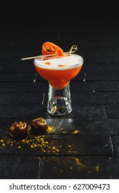 Bright orange alcohol cocktail with carrot garnish with chesnut and curcuma on black background