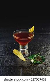 Bright orange alcohol cocktail garnished with ginger and lemon slice on black background