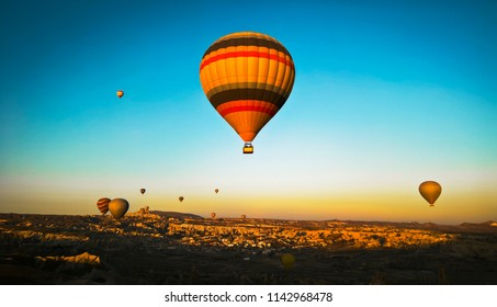 A bright orange balloon in the air at sunrise in Cappadocia, Turkey, on a background of blue, clear skies. On the background of the mountain and the city Goreme National Park. Many air balloons.