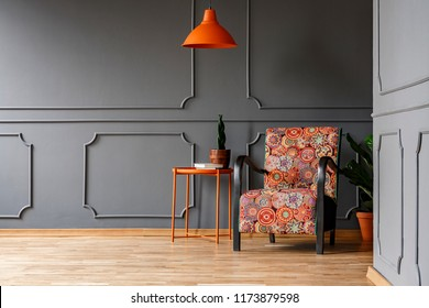 Bright orange ceiling light above a boho style armchair in an elegant living room interior with molding on gray walls and copy space place for a chair. Real photo.