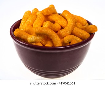 Bright orange cheese puffs in a red bowl.