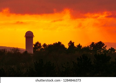 Bright orange cloudy sunset above the solar telescope tower in the Crimean astrophysical observatory