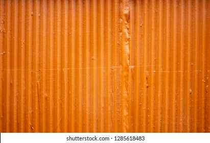 Bright orange corrugated metal zinc wall for background or texture
