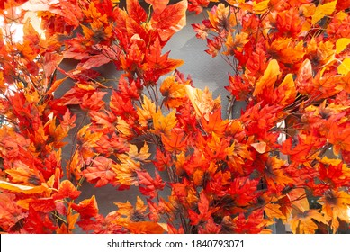 Bright orange decorative leaves on a gray wall background. Wondrous decoration