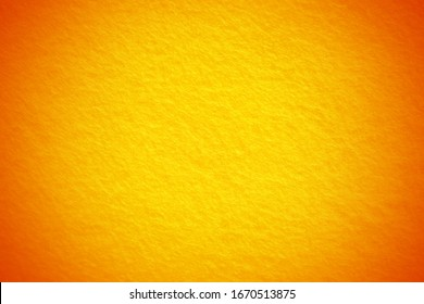 Bright orange fabric background texture with dark vignette for summer season. Blurred background with copy space for design.