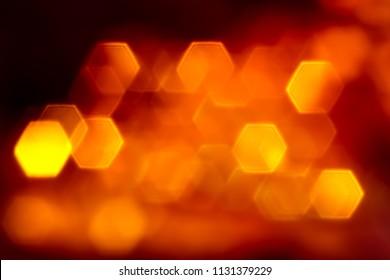Bright orange flat hexagone lights bokeh on black background