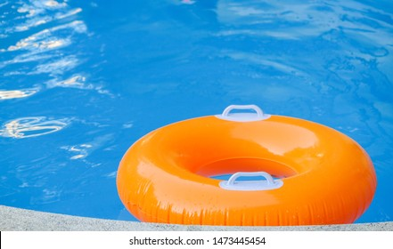A bright orange float in a blue pool, a ring floating in a refreshing blue pool with waves reflecting in the summer sun. Active holiday background. Lifeguard for the child.