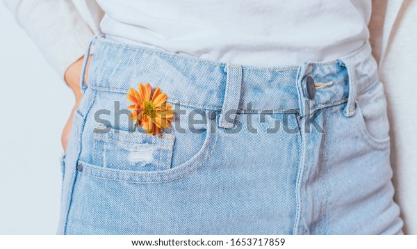 Bright orange flower in pocket blue jeans of young slender woman standing on white background, close-up.
