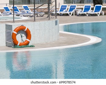 Bright orange life buoy and blue sun beds by the pool with clear clear water