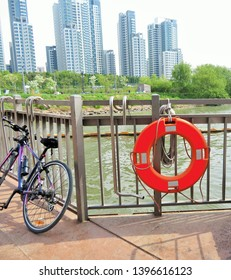 Bright orange lifesaver hanging on a railing next to a bicycle, overlooking a riverside park and residential buildings, along the Han River, in Seoul, Korea