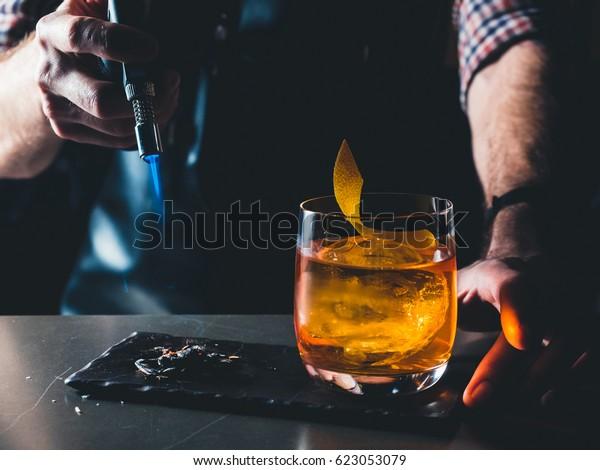 Hellorangefarbener Cocktail mit Whiskey auf schwarzem Brett. Dekoriert mit brennender Kohle und Rauch. Bartender Hand, die die Cocktaildekoration verbrannt. Perfect Serve-Beispiel. Horizontal