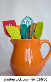 Bright orange pitcher filled with colorful utensils