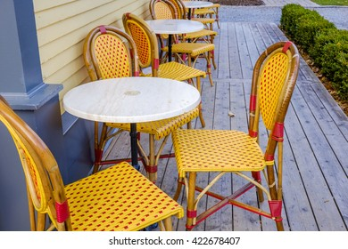 Bright orange and red plastic wicker bistro chairs surround white table outside a coffee shop.