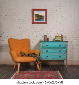 Bright orange retro armchair with plaid against white brick wall with shabby chic vintage turquoise cabinet in living room and hanged painting, with clipping path for the painting