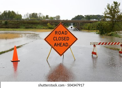 A bright orange Road Closed Ahead Sign and caution cones and barricades are blocking a rain flooded rural street.