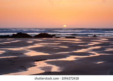 Bright orange setting sun reflects in the meandering rivulets of water on Porthtowan Beach in Cornwall, UK