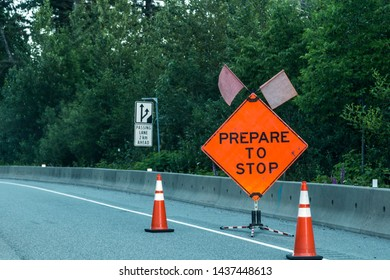 Bright orange sign that reads be prepared to stop warns a line of motorists of road construction ahead.
