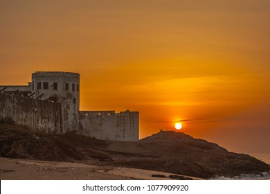 Bright orange sky on the beach of Cape Coast, Ghana. The sun rising over a rock next to the ocean and the old castle.