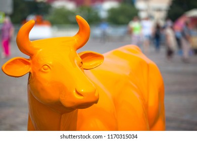 bright orange statue of a cow at a farm fair