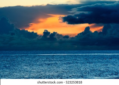 A bright orange sunset coming out from a stormy sky with blue choppy ocean