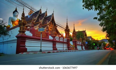 Bright Orange sunset sky in background of beutiful big golden bhudda at Wat mho come tung, chiang mai, thailand on evening 14/09/2017.