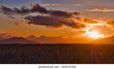 Bright orange sunset in Southeast Alaska with forest, mountains and clouds.