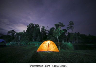 Bright orange tent in the night, blue sky. Light on a single tent
