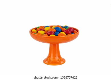 Bright Orange Vintage Fiesta Ware Pedestal Candy Serving Dish with an Assortment of Colorful Candy. Sophisticated and Isolated on White.