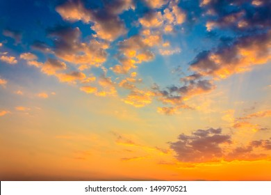Bright orange and yellow colors sunset sky / Yellow blue sunrise sky with sunlight