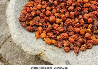 Bright orange and yellow dried sea buckthorn (Hippophae rhamnoides) berries close-up in a grey stone bowl. A healthy snack and alternative herbal medicinal product. Perennial shrub. Natural background
