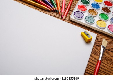 Bright paints along with the pencils and the album. Concept of education or back to school. Top view, flat lay. copyspace