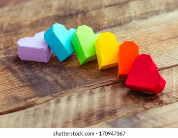 Bright paper hearts on wooden background