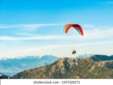 Bright paraglider floating in the air with blue sky, green hills and mountains background near Oludeniz in Turkey