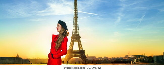 Bright in Paris. Full length portrait of happy trendy tourist woman in red coat against Eiffel tower in Paris, France