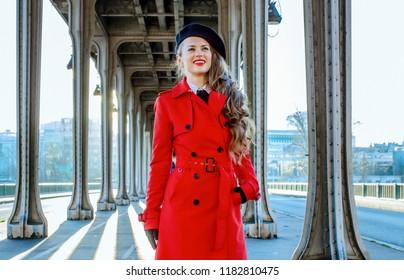 Bright in Paris. happy elegant tourist woman in red trench coat on Pont de Bir-Hakeim bridge in Paris looking into the distance