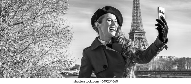 Bright in Paris. happy modern woman in red trench coat on embankment near Eiffel tower in Paris, France taking selfie