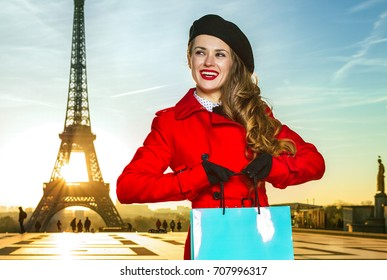 Bright in Paris. happy young tourist woman in red coat in the front of Eiffel tower in Paris, France with shopping bag looking aside