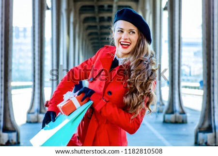 Bright in Paris. Portrait of smiling modern tourist woman in red trench coat on Pont de Bir-Hakeim bridge in Paris with shopping bag and Christmas present box looking into the distance
