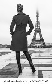 Bright in Paris. Seen from behind modern woman in red trench coat against Eiffel tower in Paris, France looking at Eiffel tower