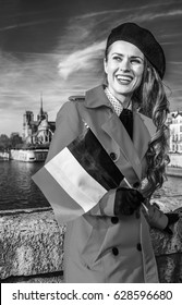 Bright in Paris. smiling stylish woman in red trench coat on embankment near Notre Dame de Paris in Paris, France with French flag looking into the distance